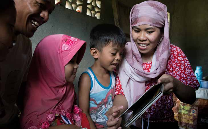 ​ Jenaica, 4, (pink headscarf), and her family read together at home, in Mindanao, Philippines. © SavetheChildren/Hannah Adcock